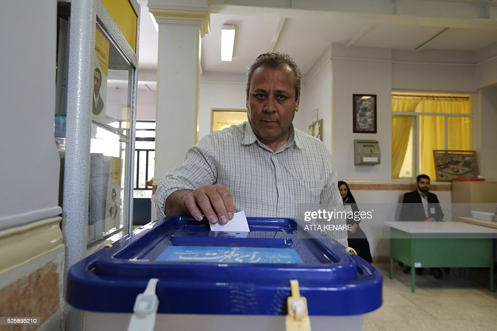 An Iranian man casts his ballot to vote in the second round of parliamentary elections at a polling station in the town of Robat Karim, some 40 kms southwest of the capital Tehran, on April 29, 2016. Iranians started voting in second round elections for almost a quarter of parliament's seats, the latest political showdown between reformists and conservatives seeking to influence the country's future. Polling stations opened at 8:00 am (0330 GMT) for the ballot which is taking place in 21 provinces, but not Tehran, because no candidate in 68 constituencies managed to win 25 percent of votes cast in initial voting on February 26. Reformists who backed moderate President Hassan Rouhani made big gains in the first round following Iran's implementation of a nuclear deal with world powers, which lifted sanctions blamed for long hobbling the economy. Conservative MPs, including vehement opponents of the West who openly criticised the landmark agreement that reined in Iran's atomic programme, lost dozens of seats and were wiped out in Tehran where reformists won all 30 places in parliament. / AFP / ATTA
