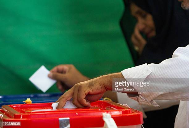 An Iranian man casts his vote in the first round of the presidential election at a polling station on June 14 2013 in Tehran Iran Four years after...