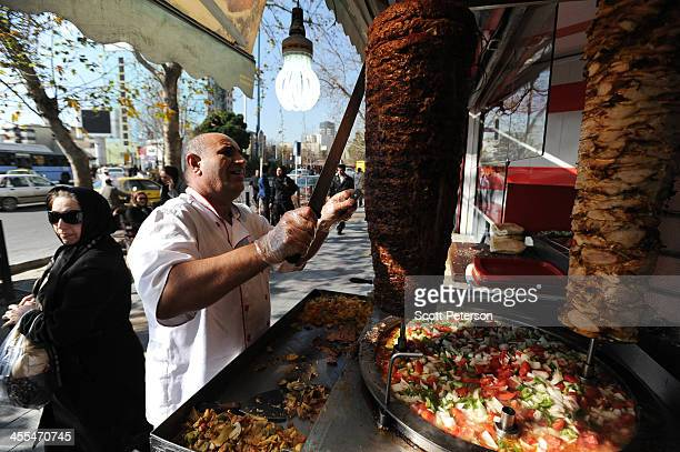 An Iranian man cuts meat for shwarma sandwiches near Vanak Square on December 8 2013 in Tehran Iran US led sanctions over Iran's disputed nuclear...
