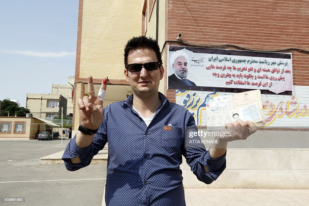 An Iranian man displays his ink-stained finger after casting his ballot for the second round of parliamentary elections at a polling station in the town of Robat Karim, some 40 kms southwest of the capital Tehran, on April 29, 2016. Iranians started voting in second round elections for almost a quarter of parliament's seats, the latest political showdown between reformists and conservatives seeking to influence the country's future. Polling stations opened at 8:00 am (0330 GMT) for the ballot which is taking place in 21 provinces, but not Tehran, because no candidate in 68 constituencies managed to win 25 percent of votes cast in initial voting on February 26. Reformists who backed moderate President Hassan Rouhani made big gains in the first round following Iran's implementation of a nuclear deal with world powers, which lifted sanctions blamed for long hobbling the economy. Conservative MPs, including vehement opponents of the West who openly criticised the landmark agreement that reined in Iran's atomic programme, lost dozens of seats and were wiped out in Tehran where reformists won all 30 places in parliament. / AFP / ATTA