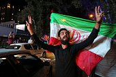 An Iranian man flashes the victory sign as an other holds the Iranian national flag during celebration in northern Tehran on July 14after Iran's...