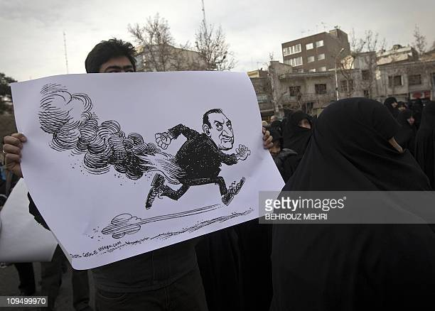 An Iranian man holds a cartoon depicting Egyptian President Hosni Mubarak during a protest following Friday prayers at Palestine Square in Tehran on...
