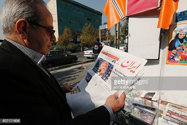 An Iranian man holds a local newspaper displaying a portrait of Donald Trump a day after his election as the new US president in the capital Tehran...