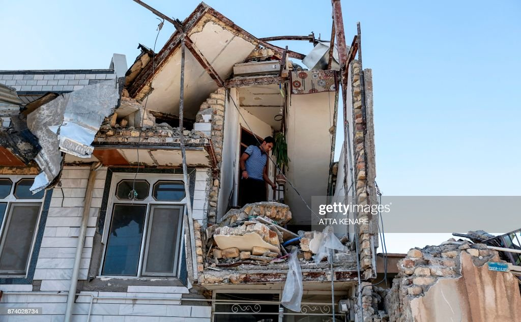 TOPSHOT - An Iranian man looks through the damaged stairwell of a building in the town of Sarpol-e Zahab in the western Kermanshah province near the border with Iraq, on November 14, 2017, following a 7.3-magnitude earthquake that left hundreds killed and thousands homeless two days before. /