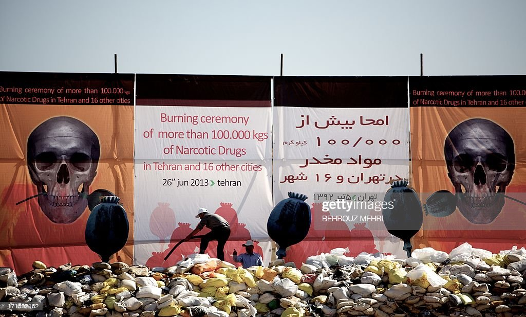 An Iranian man pours kerosene on a pile of drugs seized by authorities in recent months before setting it ablaze in eastern Tehran on June 26, 2013 to mark the International Day Against Drug Abuse and Illicit Trafficking.