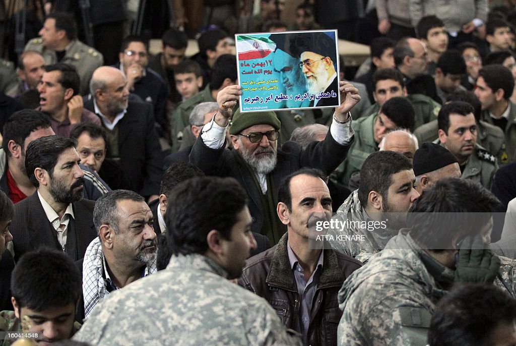An Iranian man raises a placard featuring the founder of Iran's Islamic Republic, Ayatollah Ruhollah Khomeini during a ceremony marking the 34th anniversary of his return from exile on January 31, 2013 at Khomeini's mausoleum in Tehran. Bells chimed across Iran to mark his return from exile in 1979, the trigger for a revolution which spawned an Islamic state now engulfed in a deep political crisis.
