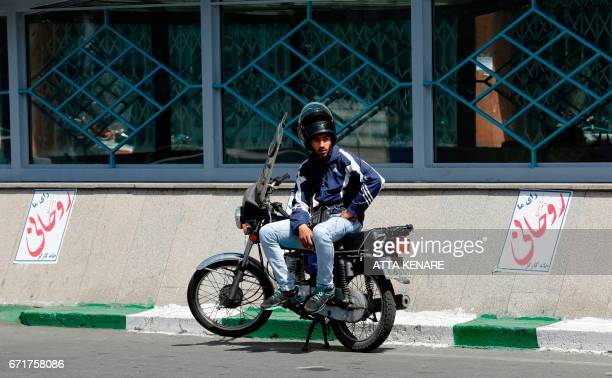 An Iranian man sits on a motorcycle between election posters of President Hassan Rouhani who is running for the presidential elections in Tehran on...