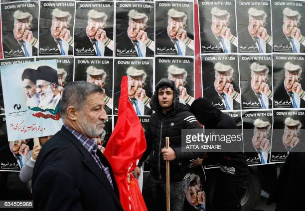 An Iranian man stands in front of placards showing a caricature of US President Donald Trump being punched by a hand wearing a bracelet of the...