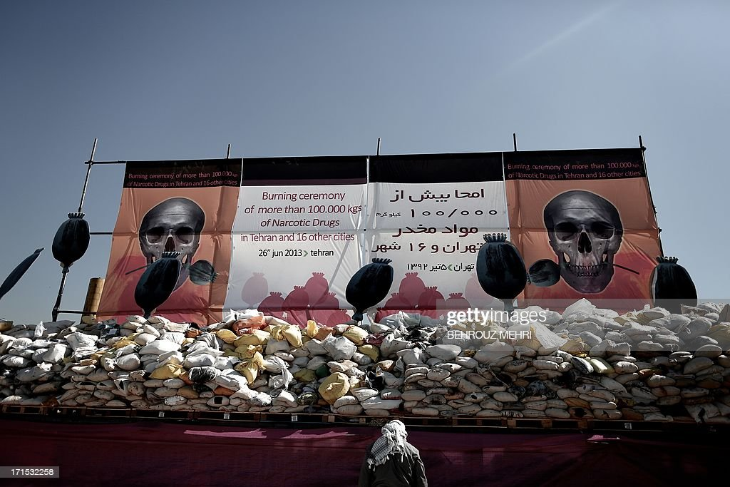 An Iranian man stands next to a pile of drugs seized by authorities in recent months before setting it ablaze in eastern Tehran on June 26, 2013 to mark the International Day Against Drug Abuse and Illicit Trafficking.