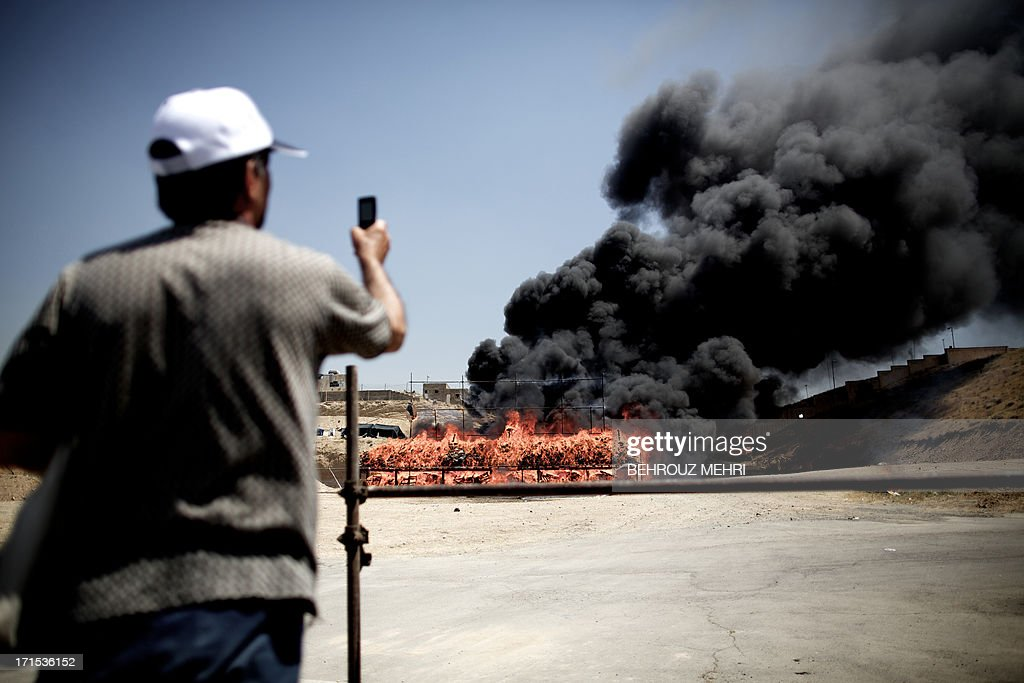 An Iranian man takes a picture of 50 tons of drugs seized in recent months burning in eastern Tehran on June 26, 2013 to mark the International Day Against Drug Abuse and Illicit Trafficking.