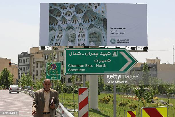 An Iranian man walks past a billboard in the capital Tehran on May 6 2015 displaying art pieces from local and foreign artists as well as...
