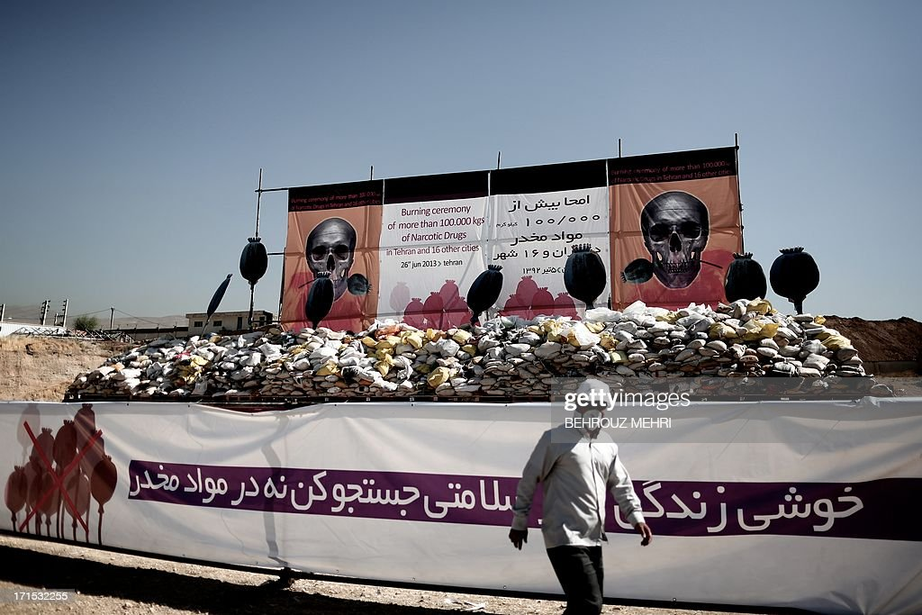An Iranian man walks past a pile of drugs seized by authorities in recent months before setting it ablaze in eastern Tehran on June 26, 2013 to mark the International Day Against Drug Abuse and Illicit Trafficking.