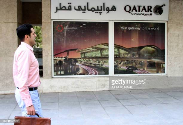 An Iranian man walks past a Qatar Airways branch in the capital Tehran on June 6 2017 A ban on Qatari flights imposed by Saudi Arabia and its allies...