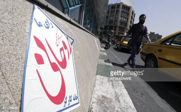 An Iranian man walks past election posters of President Hassan Rouhani who is running for the presidential elections in Tehran on April 23 2017 / AFP...