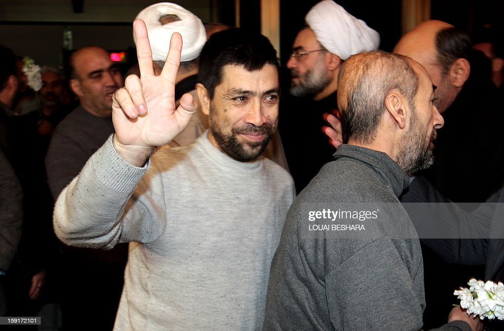 An Iranian man who had been held hostage by Syrian rebels since early August makes the victory sign as he arrives with others at a hotel in Damascus after being freed in a prisoner swap on January 9, 2013. A total of 48 Iranians were released in the unprecedented exchange for 2,130 prisoners detained by President Bashar al-Assad's regime, according to several sources. AFP PHOTO/LOUAI BESHARA