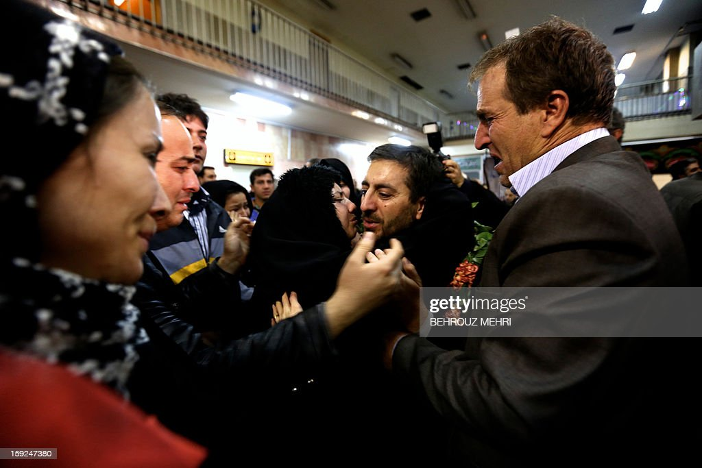 An Iranian man who has been held hostage, alongside 48 other Iranians, by Syrian rebels since early August 2012, hugs family members after arriving at Tehran's Mehrabad airport on January 10, 2013. The rebels agreed to swap the 48 Iranians, described by the Islamic republic as pilgrims but by the rebels and Washington as members of Iran's elite Revolutionary Guards, for more than 2,000 detainees held by the Syrian regime. AFP PHOTO / BEHROUZ MEHRI