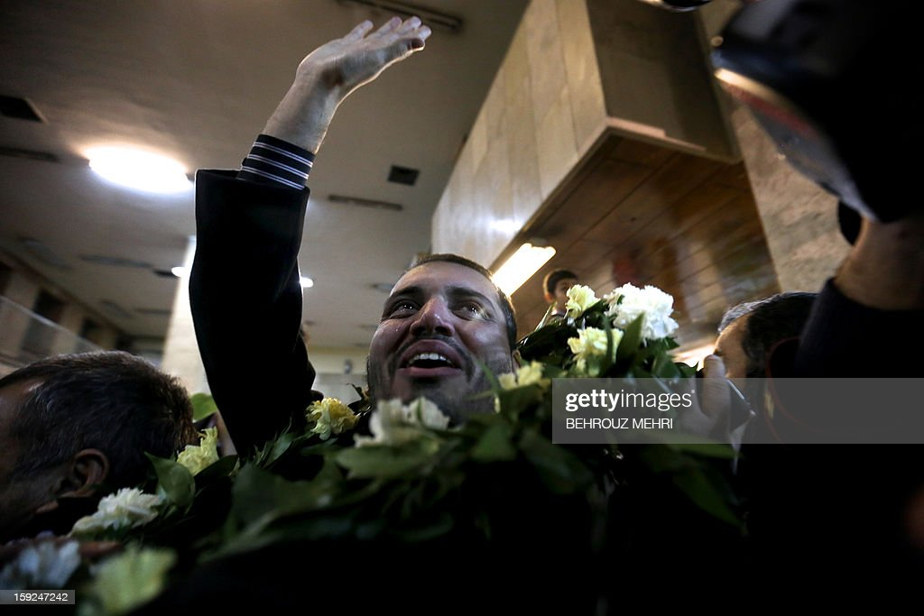 An Iranian man who has been held hostage by Syrian rebels since early August 2012 waves to his family as he cries after arriving at Tehran's Mehrabad airport on January 10, 2013. The rebels agreed to swap the 48 Iranians, described by the Islamic republic as pilgrims but by the rebels and Washington as members of Iran's elite Revolutionary Guards, for more than 2,000 detainees held by the Syrian regime.