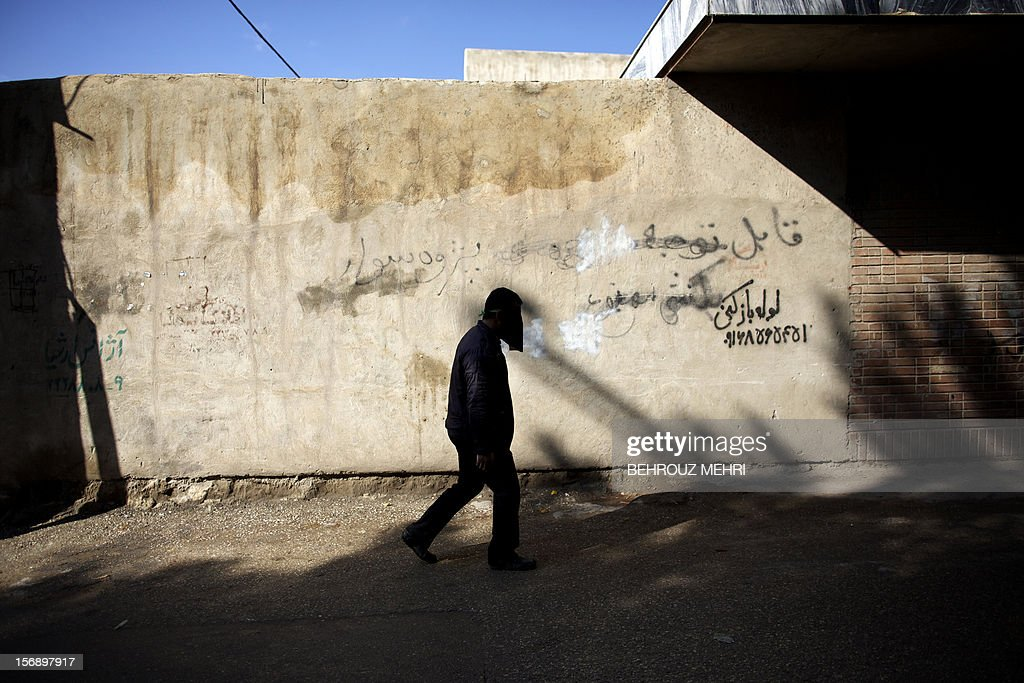 An Iranian man with his face covered with a religious Niqab walks in a street during the 'Chehel Manbar' (Forty Pulpits) ritual a day before Ashura, in the city of Khorramabad, 470 kilometres southwest of Tehran on November 24, 2012. Traditionally, Iranian women of Khorramabad walk bare-foot to light candles in 40 designated places in the city centre on the eve of the Ashura, which marks the seventh century slaying of the grandson of Prophet Mohammed, Imam Hussein.