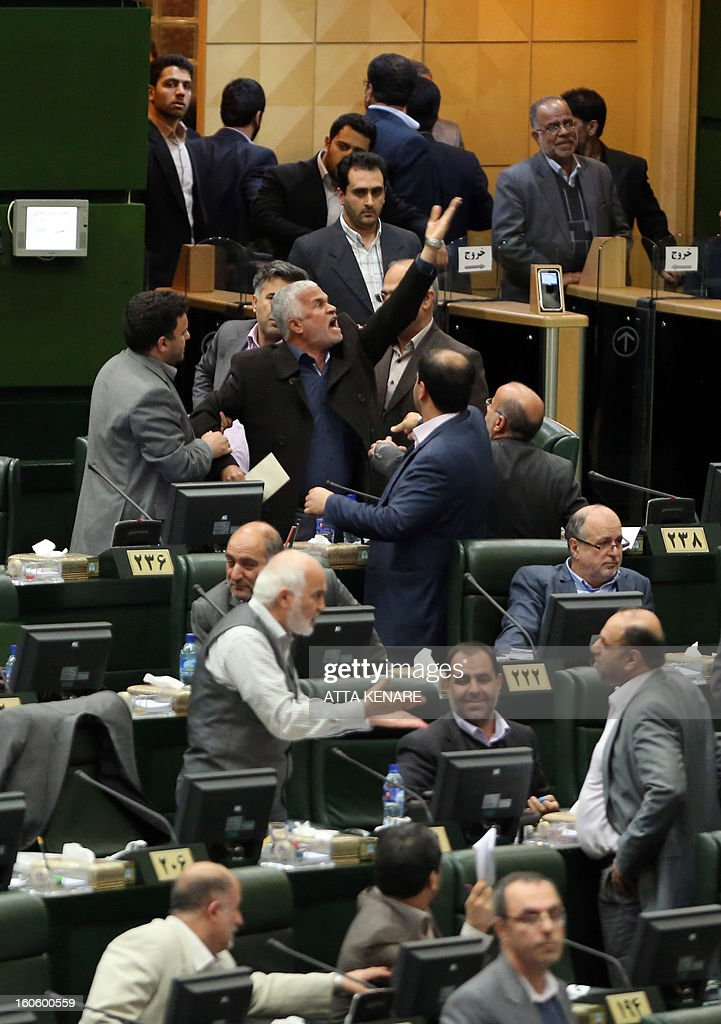 An Iranian Member of Parliament (MP) objects as President Mahmoud Ahmadinejad delivers a speech to the parliament in Tehran on February 3, 2013. A large majority of MPs voted in a heated parliament session, broadcast on state radio, to remove the labour and social welfare minister, Abdolreza Sheikholeslam, for refusing to sack a controversial figure, Saeed Mortazavi. AFP PHOTO/ATTA KENARE