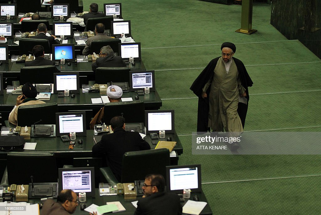 An Iranian Member of Parliament (MP) walks in the parliament in Tehran on February 3, 2013, as the Iranian President delivers a speech. Bad blood between Iran's government and parliament spilled into open over the impeachment of a minister, with heads of the two branches accusing each other of corruption and abuse of power.
