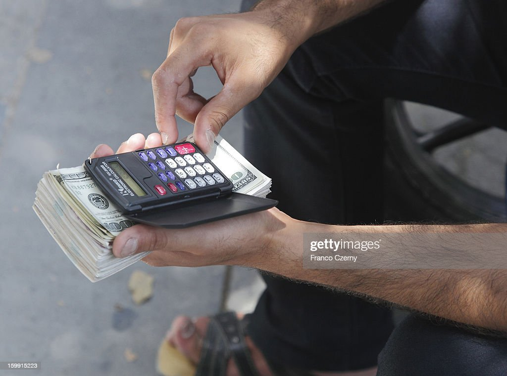An iranian money dealer counts US currency on August 13, 2012 in Tehran, Iran.