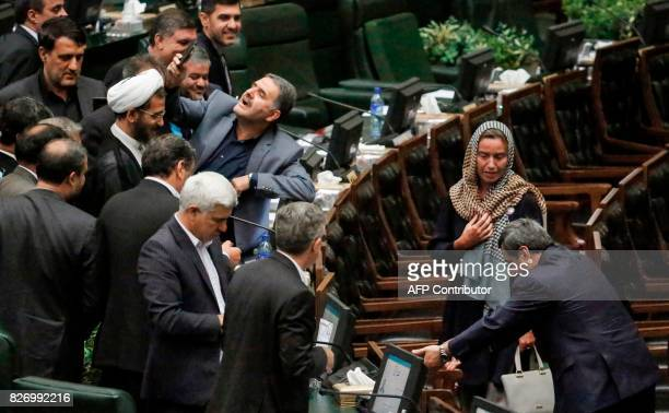 An Iranian MP uses a cell phone to take a 'selfie' picture as EU foreign policy chief Federica Mogherini walks by during the ceremony for the...