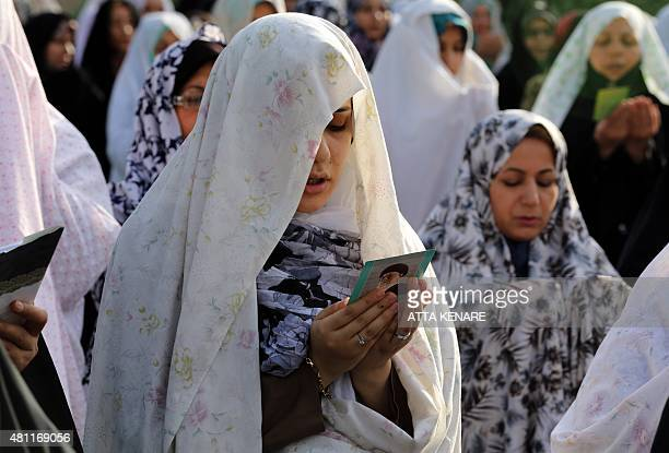 An Iranian Muslim woman reads from a card bearing a portrait of Iran's supreme leader Ayatollah Ali Khamenei as she performs the Eid alFitr prayers...
