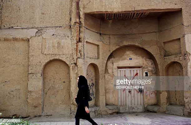 An Iranian Muslim woman walks past an abandoned Armenian house in the Julfa neighbourhood in the historic city of Isfahan some 400 kms south of the...