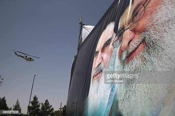 An Iranian police helicopter passes above portraits of Iran's supreme leader Ayatollah Ali Khamenei and the former Ayatollah Khomeini outside...