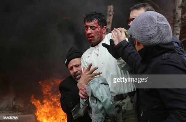 An Iranian police officer is taken away by people after allegedly being beaten by opposition supporters during an antigovernment protest in Tehran on...