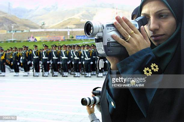 An Iranian police woman films President Mohammad Khatami's speech during a gradation ceremony at Tehran's police academy 04 October 2003 Iran...