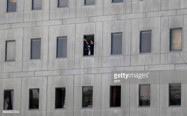 An Iranian policeman holds a weapon as another one gestures from a window at the Iranian parliament in the capital Tehran on June 7 2017 during an...