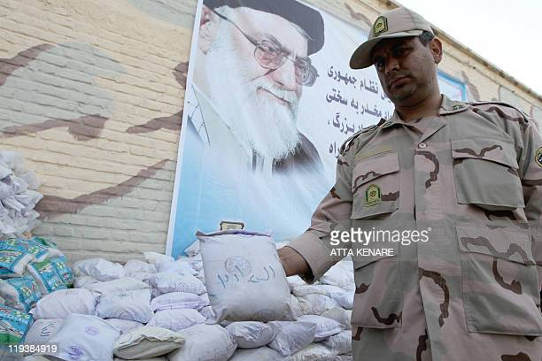 An Iranian policeman holds up a package of seized Afghanmade drugs during a media tour in the southeastern city of Zahedan on July 19 2011 The UN...