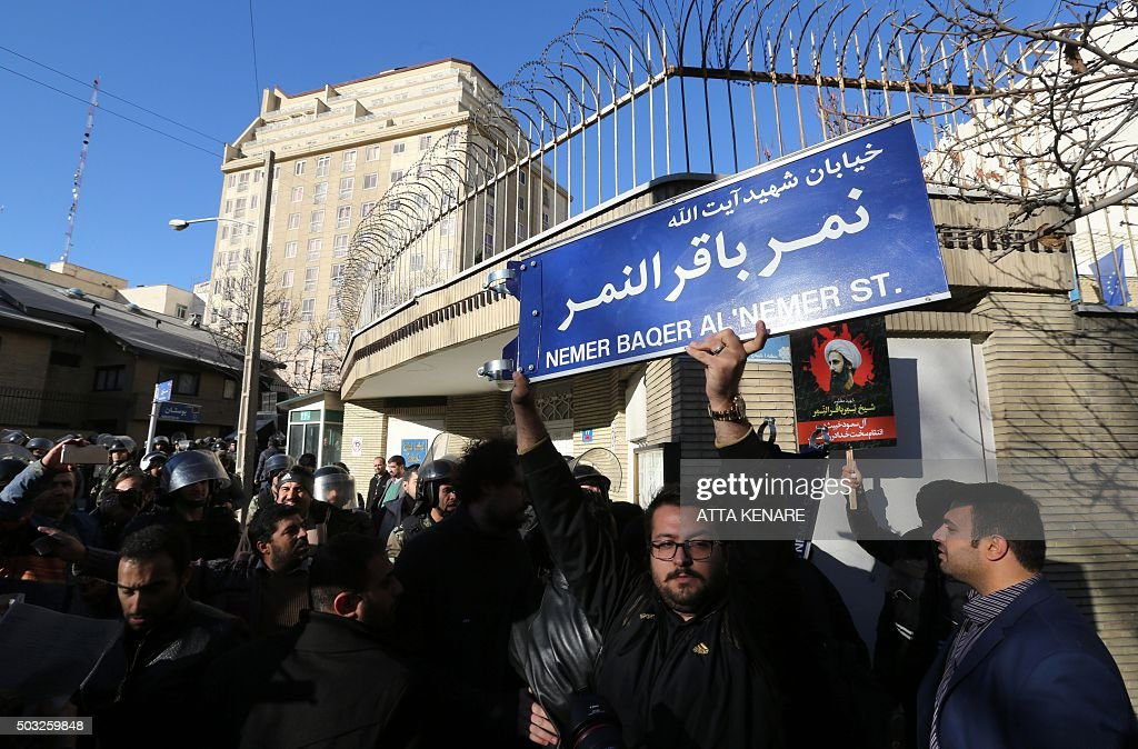 An Iranian protester holds a street sign bearing the name of prominent Shiite Muslim cleric Nimr alNimr during a demonstration against his execution...
