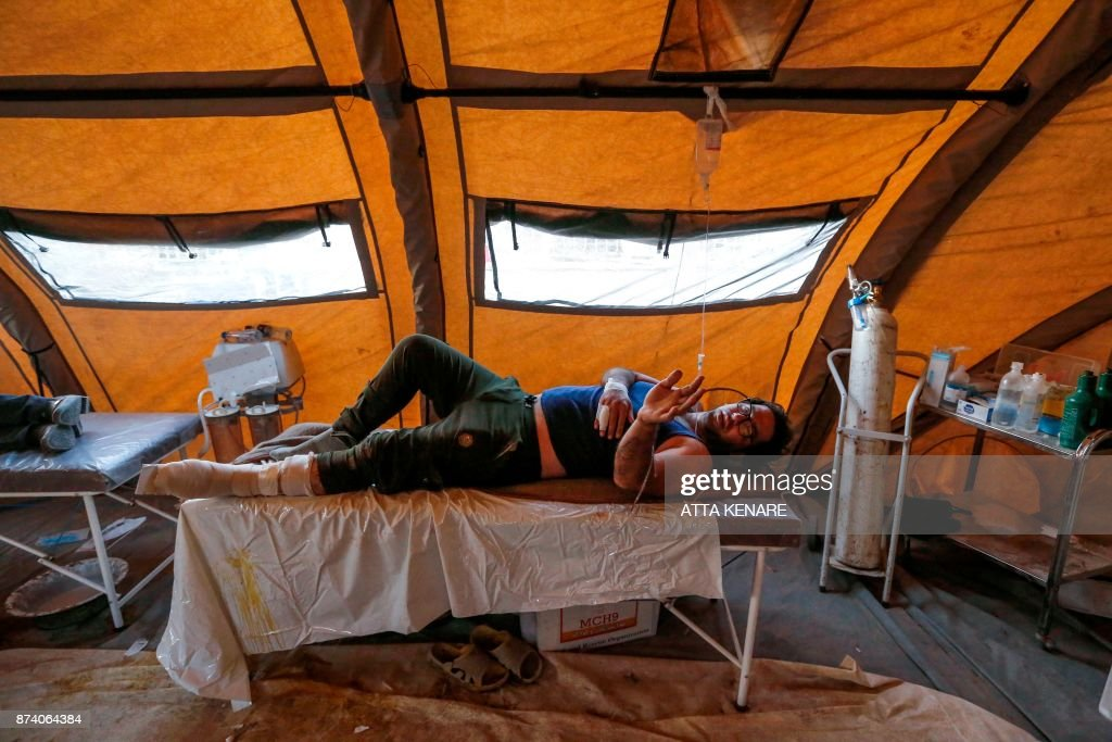 TOPSHOT - An Iranian quake victim lies on an operating bed after receiving treatment at a field hospital in the town of Sarpol-e Zahab in the western Kermanshah province near the border with Iraq, on November 14, 2017, following a 7.3-magnitude earthquake that left hundreds killed and thousands homeless two days before. /