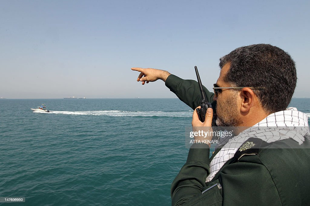 An Iranian Revolutionary Guard gives directions to speedboats on the water during a ceremony to commemorate the 24th anniversary of the downing of Iran Air flight 655 by the US navy, at the port of Bandar Abbas on July 2, 2012. The plane was shot down by mistake over the Gulf by the US navy's guided missile cruiser, USS Vincennes, during confrontation with Iranian speedboats on July 3, 1988, killing 290 civilian passengers and crew members.