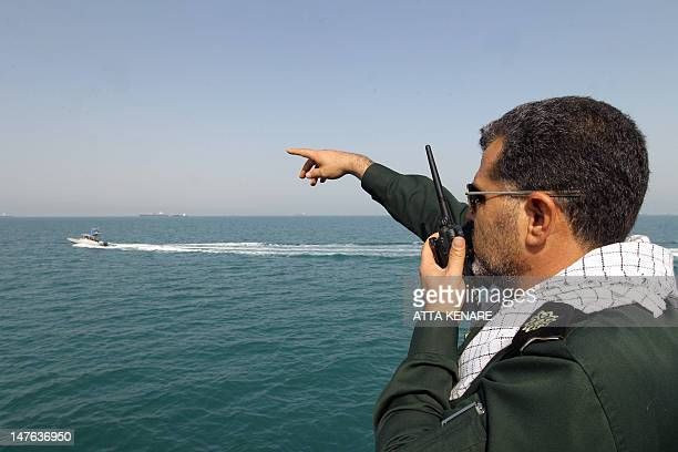An Iranian Revolutionary Guard gives directions to speedboats on the water during a ceremony to commemorate the 24th anniversary of the downing of...