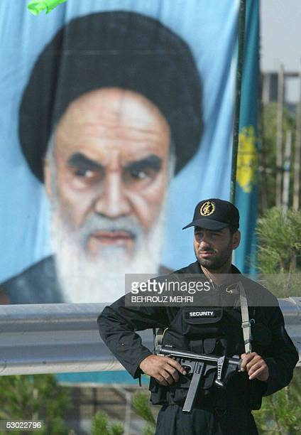 An Iranian security guard stands guard next to a portrait of Iran's founder of the Islamic Republic Ayatollah Ruhollah Khomeini during a military...
