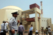 An Iranian security man stands next to journalists outside the reactor building at the Russianbuilt Bushehr nuclear power plant in southern Iran on...