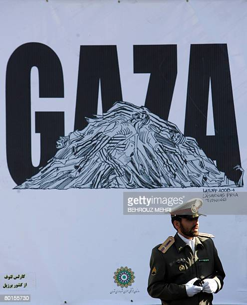 An Iranian security officer stands in front of a mural cartoon by Carlos Lattuf of Brazil on Gaza during a protest in Palestine square in Tehran on...