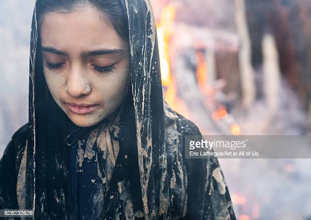An Iranian shiite muslim girl with closed eyes stands in front a bonfire after rubbing mud on her chador during the Kharrah Mali ritual to mark the...