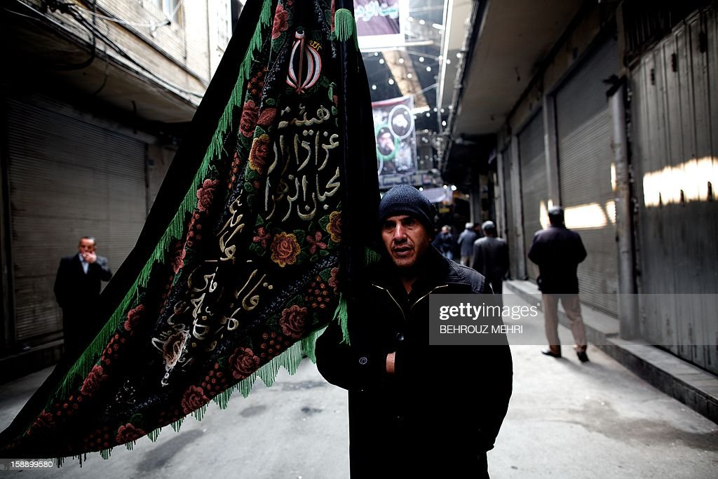 An Iranian Shiite Muslim holds a religious banner during the Arbaeen religious festival at Tehran's Grand Bazaar, on January 3, 2013 to mark the 40th day after Ashura, commemorating the seventh century killing of Prophet Mohammed's grandson, Imam Hussein.