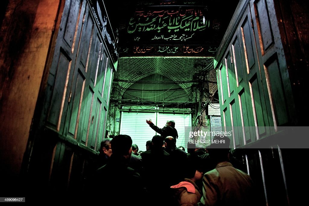 An Iranian Shiite Muslim panegyrist sings religious songs at Tehran's Grand Bazaar on December 23 2013 during the Arbaeen religious festival which...