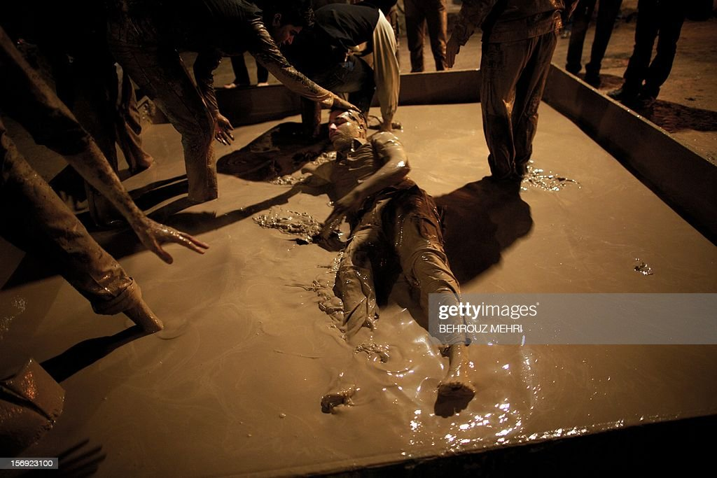 An Iranian Shiite Muslim rolls over in a mud pond during the 'Kharrah Mali' (Mud Rubbing) ritual to mark the Ashura religious ceremony in the city of Khorramabad, some 470 kms southwest of Tehran on November 25, 2012. 'Khrreh Mali' or 'Mud Rubbing' is a ritual that is held in the city of Khorramabad every year to commemorate the seventh century slaying of Prophet Mohammed's grandson Imam Hussein, in which Iranian men roll over in mud and dry themselves by gathering around the bonfires before flagellating themselves.