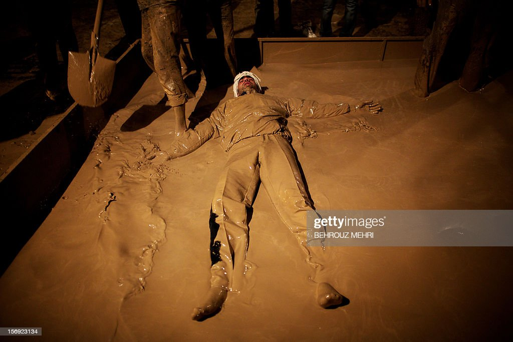 An Iranian Shiite Muslim rolls over in a mud pond early in the morning during the 'Kharrah Mali' (Mud Rubbing) ritual to mark the Ashura religious ceremony in the city of Khorramabad, some 470 kms southwest of Tehran on November 25, 2012. 'Khrreh Mali' or 'Mud Rubbing' is a ritual that is held in the city of Khorramabad every year to commemorate the seventh century slaying of Prophet Mohammed's grandson Imam Hussein, in which Iranian men roll over in mud and dry themselves by gathering around the bonfires before flagellating themselves.