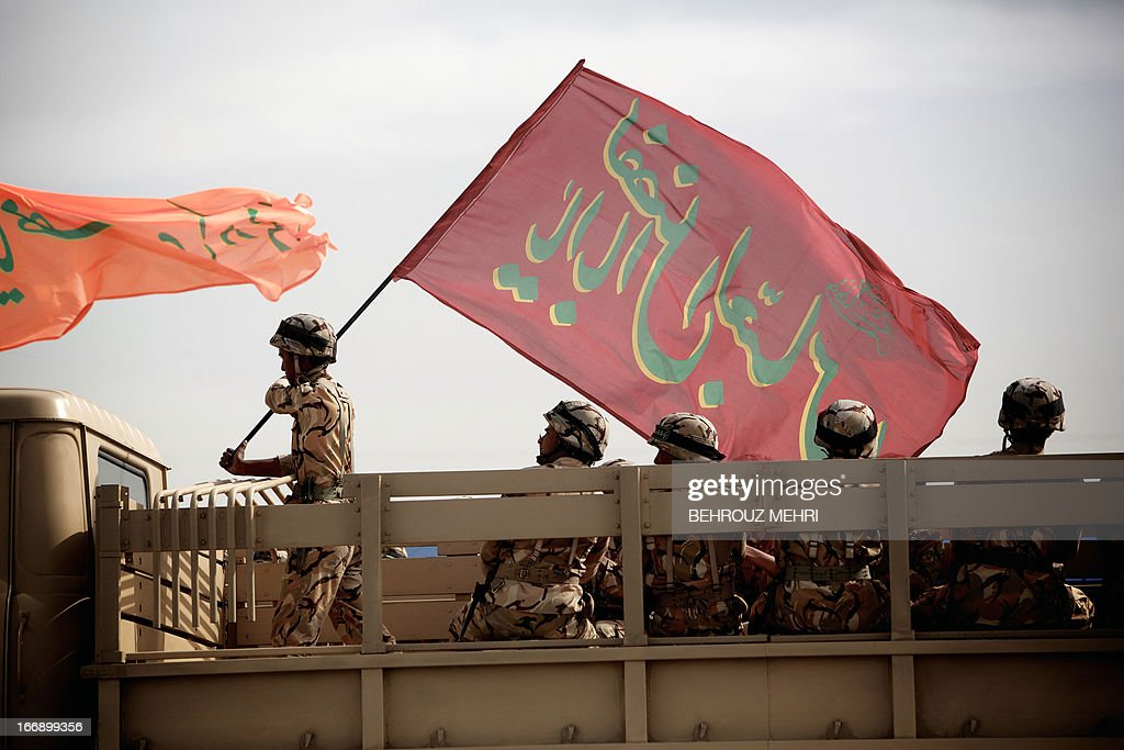 An Iranian soldier holds a religious banner on the back of a pick-up truck during the Army Day parade in Tehran on April 18, 2013. The Iranian army 'alone' is able to destroy Israel, Tehran's regional arch foe, Islamic republic army commander general Ataollah Salehi said, on the sideline of the country's annual Army Day.