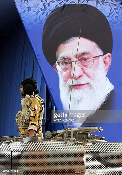 An Iranian soldier parades on a tank in front of a banner bearing the portrait of Iran's supreme leader Ayatollah Ali Khamenei displayed on the...
