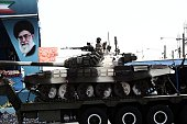An Iranian soldier sitting atop a T72 tank as it rolls past a portrait of Iran's supreme leader Ali Khamenei during the Army Day parade in Tehran on...