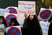 An Iranian student holds a placard reading 'Nuclear energy is our absolute right' during a demonstration outside the Tehran Research Reactor in the...