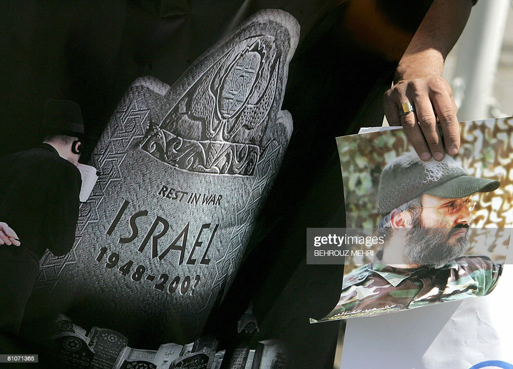 An Iranian student holds an antiIsraeli poster and a picture of assassinated Hezbollah commander Imad Mughnieh during a protest against the 60th...